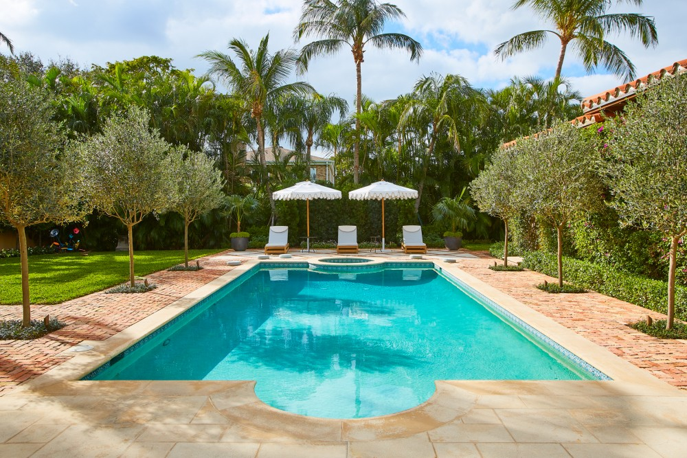 A well-defined symmetry in the pool deck pays homage to the home's Mediterranean style, including olive trees along the pool's edge and manicured hedges.