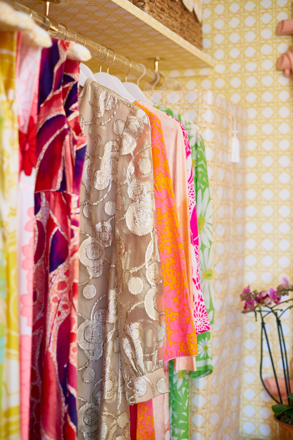 A vintage macramé-inspired wallpaper pattern offers an inspirational template and backdrop for an exuberant wardrobe.