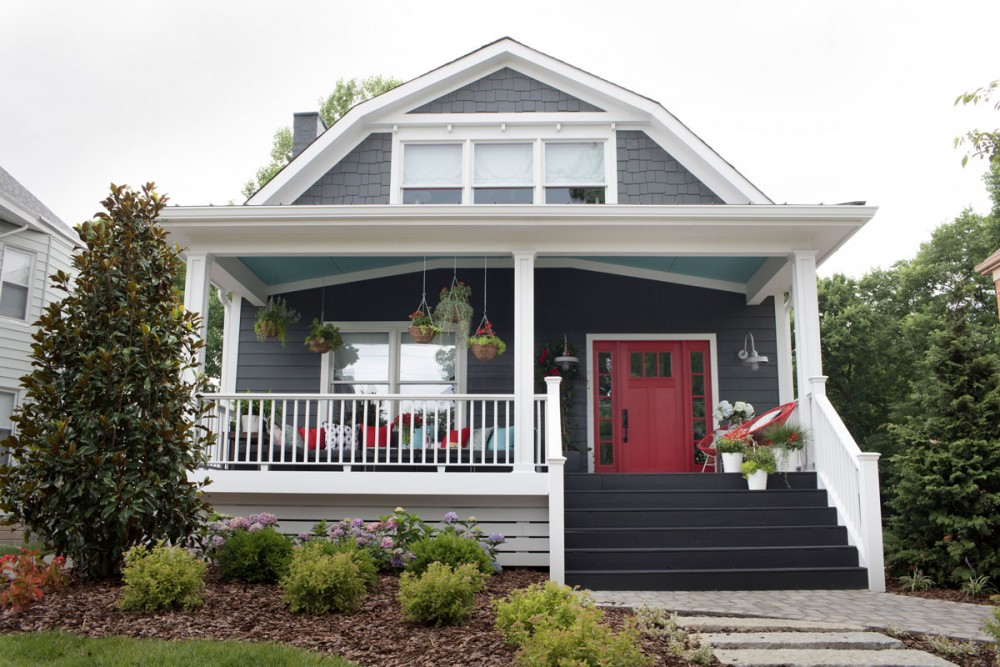 Pure white trim and charcoal gray siding create a substantive and buttoned-up backdrop for the playful yet restrained use of reds and turquoise. Colorful hydrangeas and hanging arrangements connect this home to its natural environment.