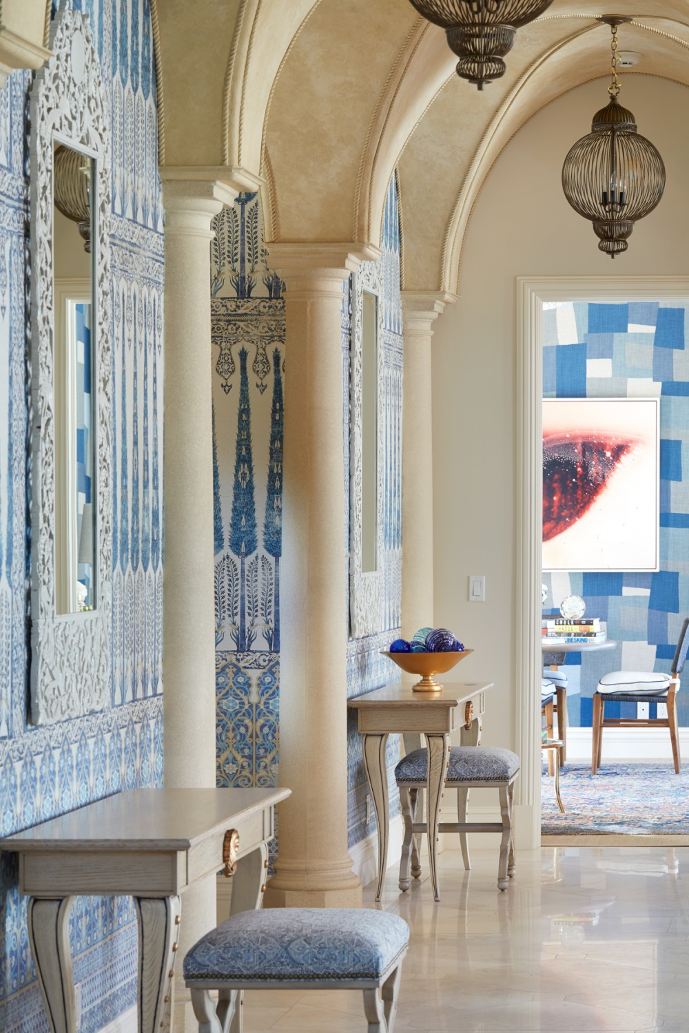 Moroccan-influenced arches along with patterned grasscloth wallpaper and panels exude a welcoming warmth in the home's entryway.