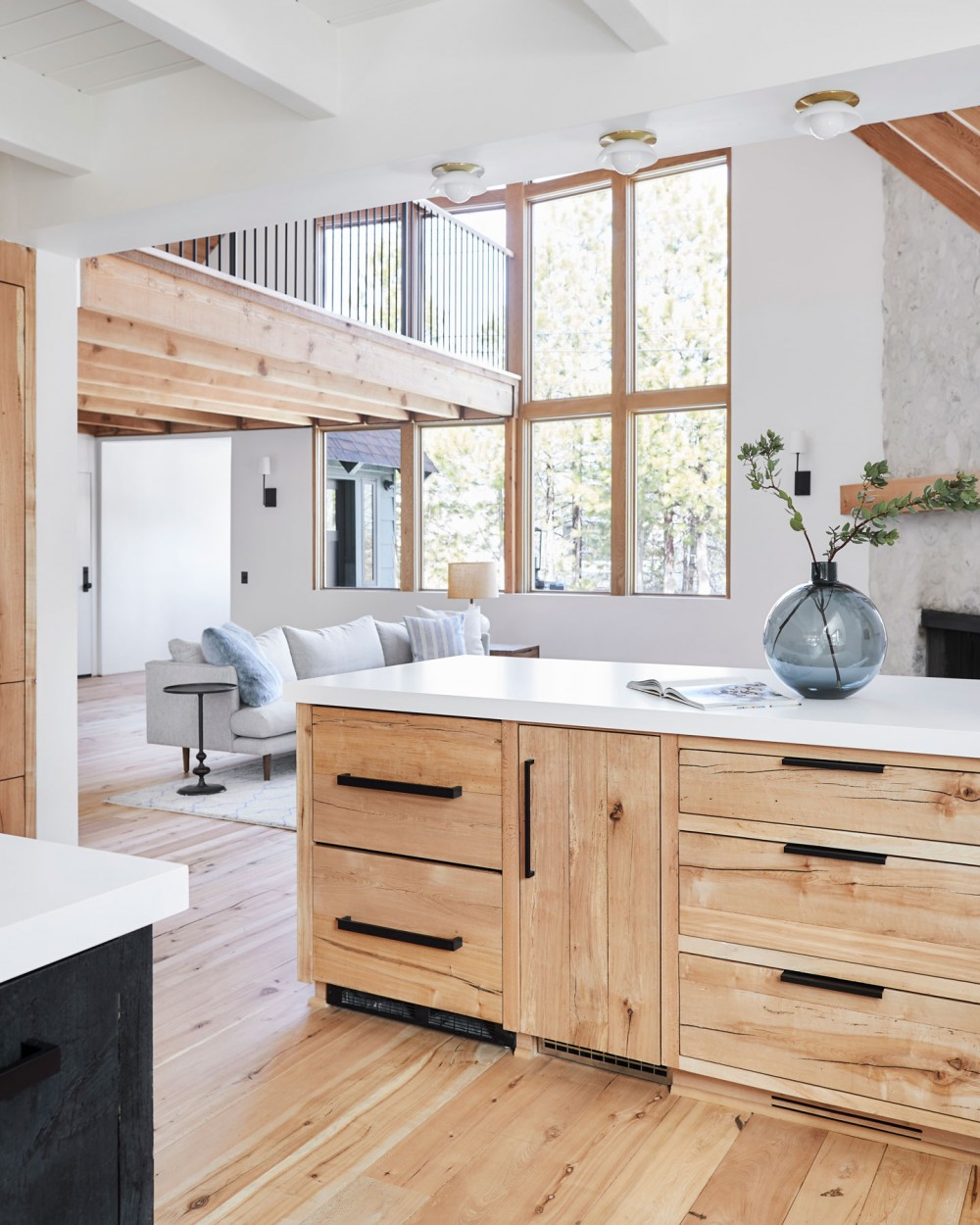 Matching wood floors and cabinetry create a welcoming rustic look, while the black hardware adds a sleek, modern touch.