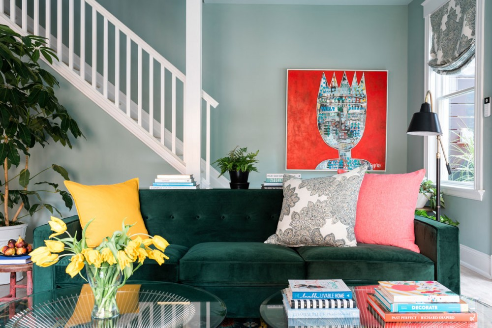 The plush emerald green sofa takes center stage in this eclectic living room, graciously sharing that roll with a lively and diverse supporting cast of cut flowers and original artwork.
