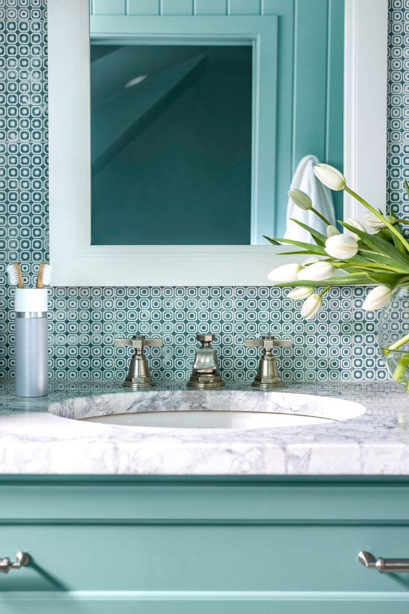 Pinstripe faucet    Verticyl sink   The patchwork porcelain wall tiles add a touch of playfulness that perfectly complements the Carrera marble top vanity and art deco-inspired Pinstripe faucet.