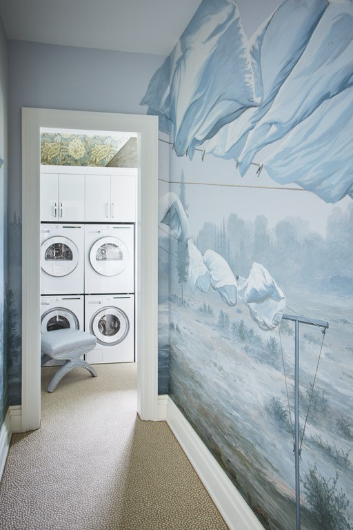 A hand-painted seascape mural offers a nostalgic entryway into the highly functional laundry room.