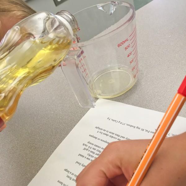 Kids measuring canola oil for healthy breakfast bars on eatlivetravelwrite.com