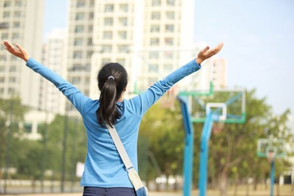 cheering woman student open arms at campus