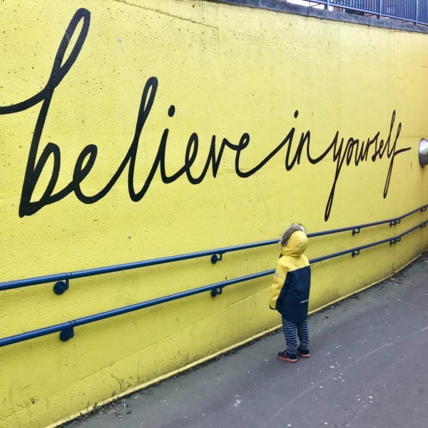 kid looking up to painted mural with inspirational quote