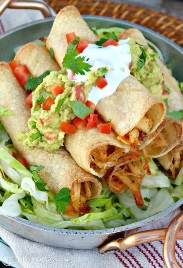 Baked Chicken Taquitos filled with seasoned shredded chicken and cheese! Add your favorite toppings and enjoy at your next fiesta! he Foodie Affair