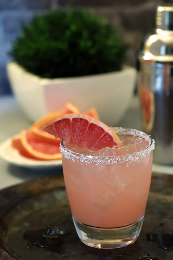 A cocktail made with vodka and grapefruit juice sits on a tray.