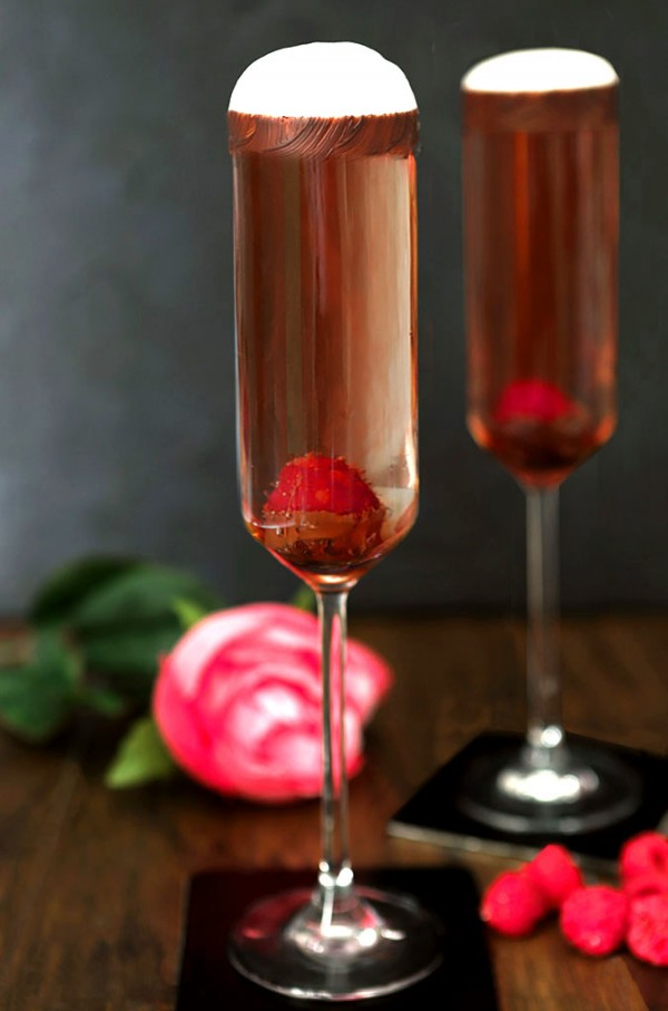 Sparkling Rosé Wine is poured int glasses decorated with chocolate and fresh raspberries.