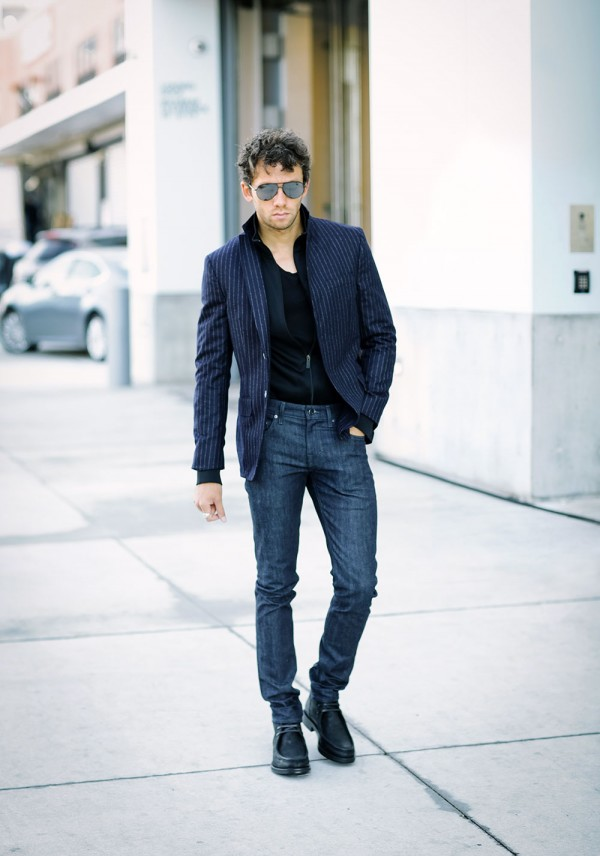 Talun Zeitoun wearing a chalk stripe blazer, track jacket, indigo denim jeans, and boots