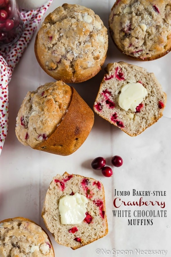 Overhead shot of Jumbo Cranberry White Chocolate Muffins scattered on a white board with one muffin cut open and a pat of butter on top.