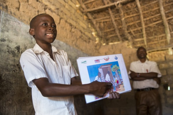 Tibu stands at the top of his class, demonstrating good hygiene procedures with flip chart