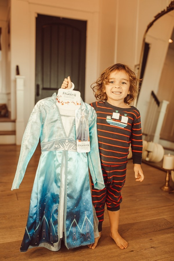 toddler holding up a costume dress