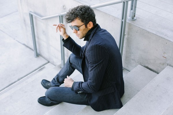 Talun Zeitoun wearing a chalk stripe blazer, track jacket, indigo denim and boots