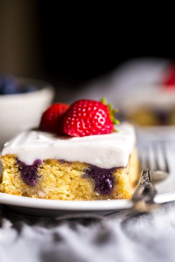 Paleo Poke Cake with Blueberries, Strawberries and Coconut Cream - The sweet pockets of homemade blueberry filling make this cake SO moist! It's topped with whipped coconut cream and strawberries for an easy, healthier dessert that is perfect for July 4th!   Foodfaithfitness.com   @FoodFaithFit