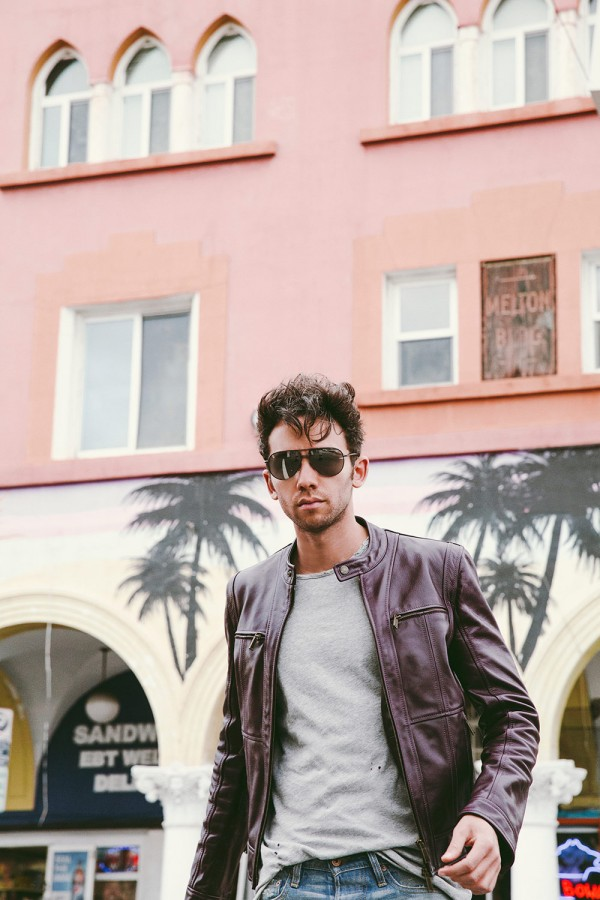 Talun Zeitoun wearing a red leather jacket and faded denim jeans in Venice Beach, CA