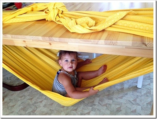 Make a hammock with a blanket tied around a table