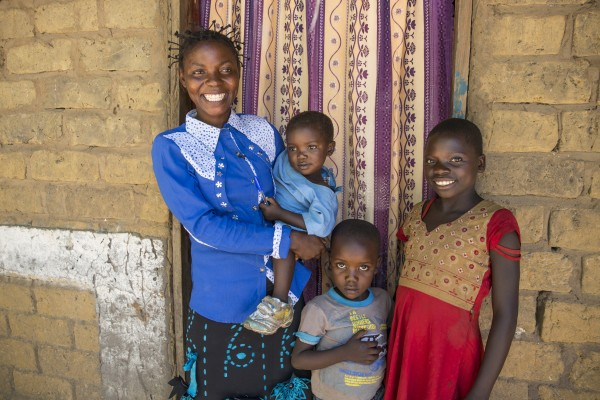 Joelle Inamulongo stands in the doorway of her home in DRC with her three children