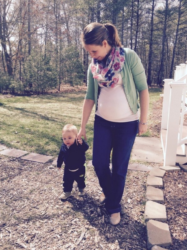 Pregnant woman in infinity scarf, cardigan, and jeans walking with toddler boy