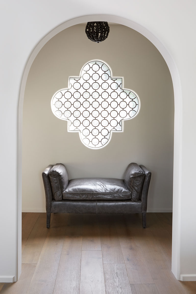 Moorish design elements frequently make an appearance in Spanish Revival homes, captured perfectly in this simple vignette with its arched doorway and ornate window.