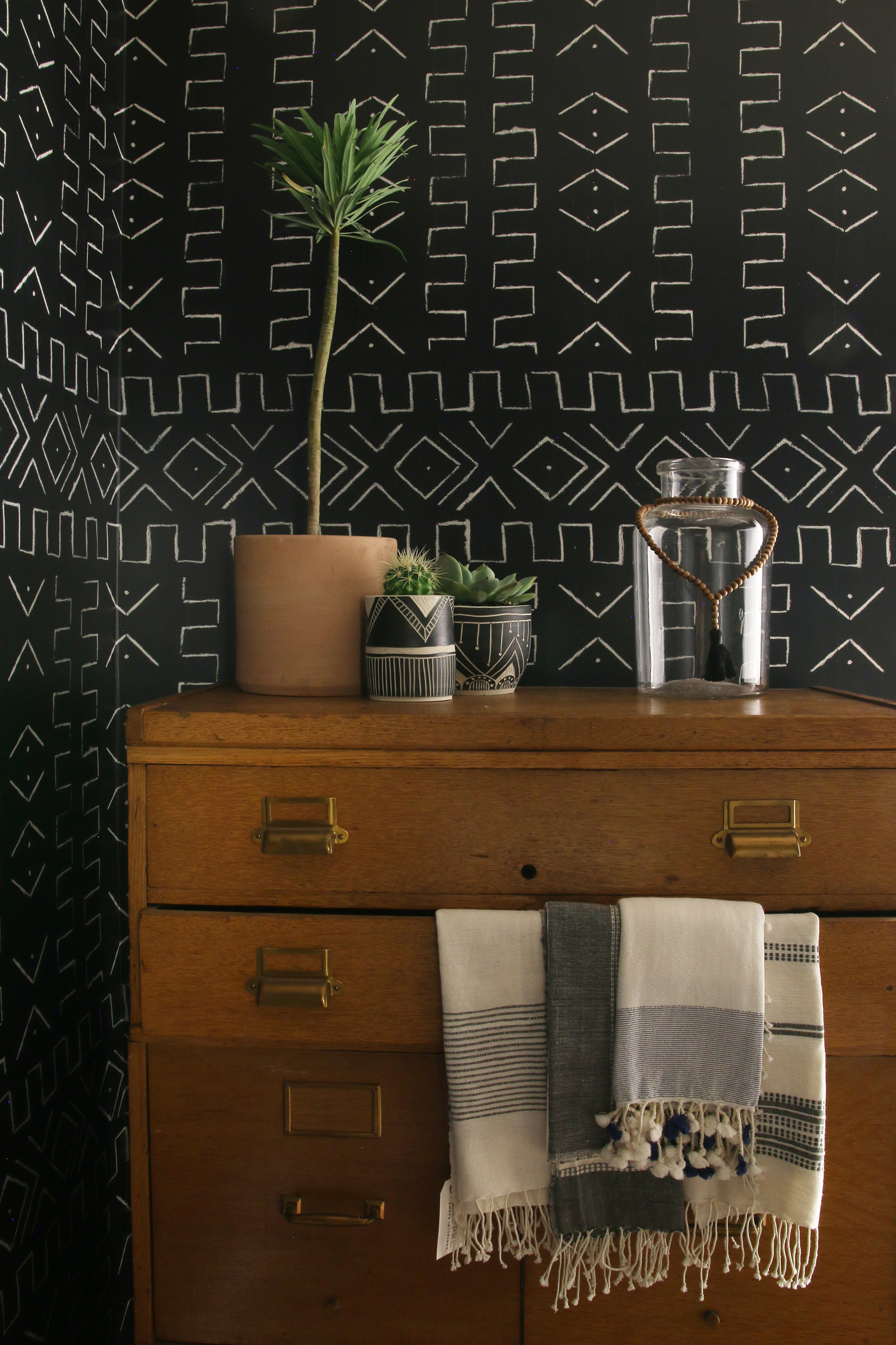 Planters and hand towels designed by Lewis further infuse the room with varying textures. The tribal-print wallpaper and a vintage dresser team up for the kind of signature and eclectic look her clients covet.