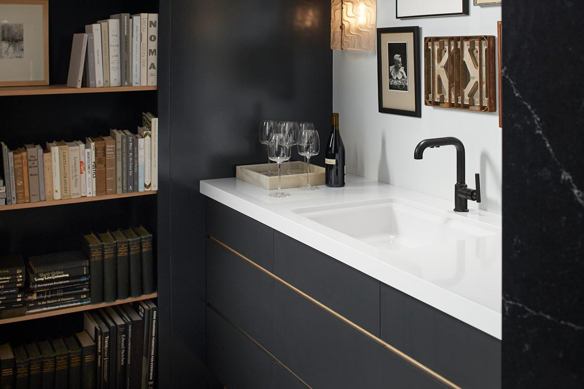 Riverby Bar Sink     Purist Faucet      A palette of black with gold accent trim offsets the bar nook from the adjacent kitchen, creating nuance and subtle character difference between rooms that are openly connected.