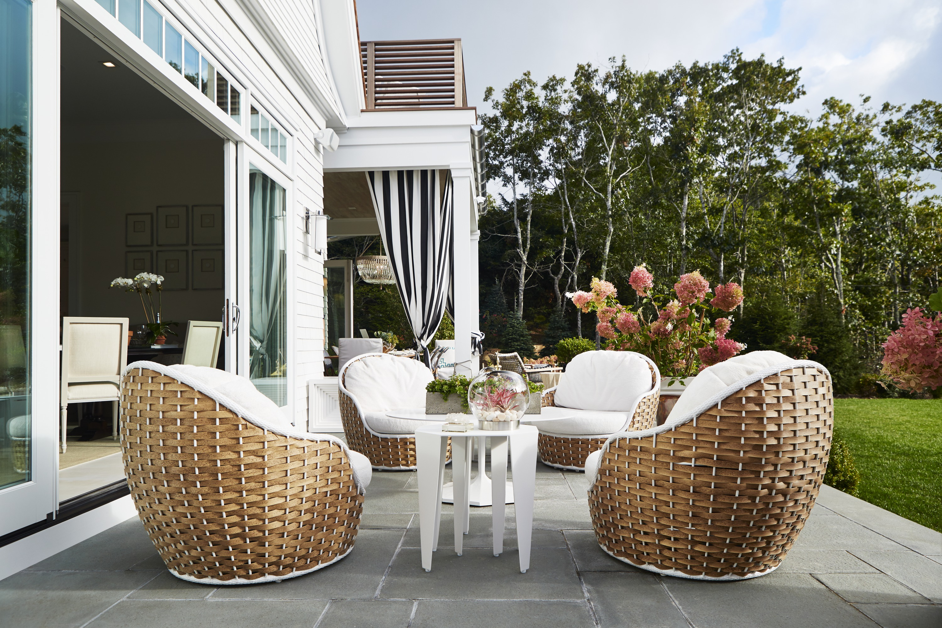 The terrace seating area, created by the Baltimore Design Group, carries the relaxed luxury of the great room outside using contemporary woven oversized chairs.