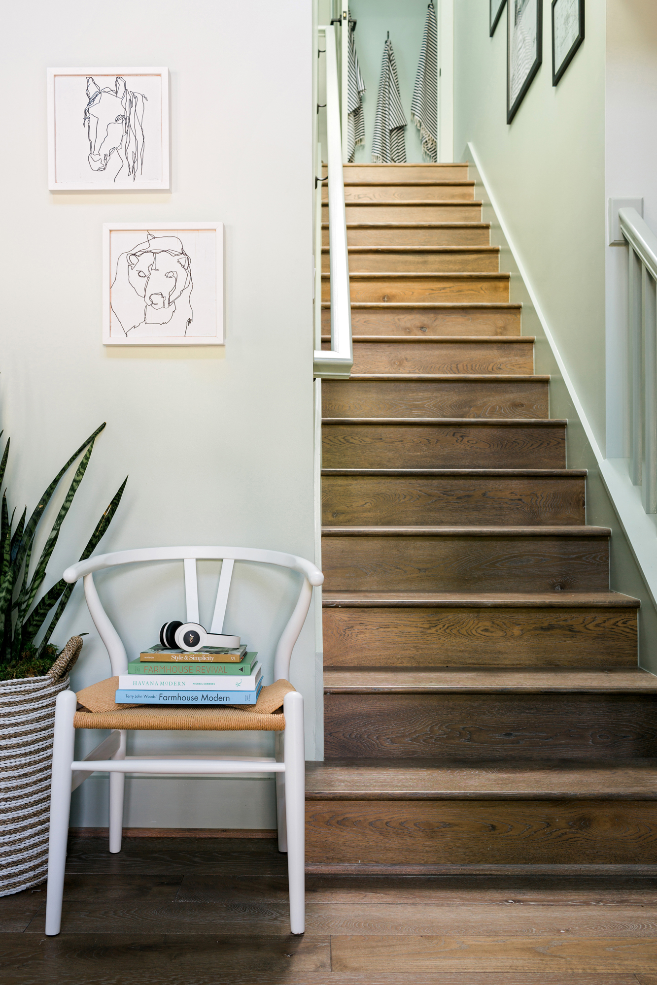 Directly across from the front entry, the stairwell sets the tone for the entire home. With a pale neutral palette, light oak floors and understated artwork, the mood is bright and inviting.