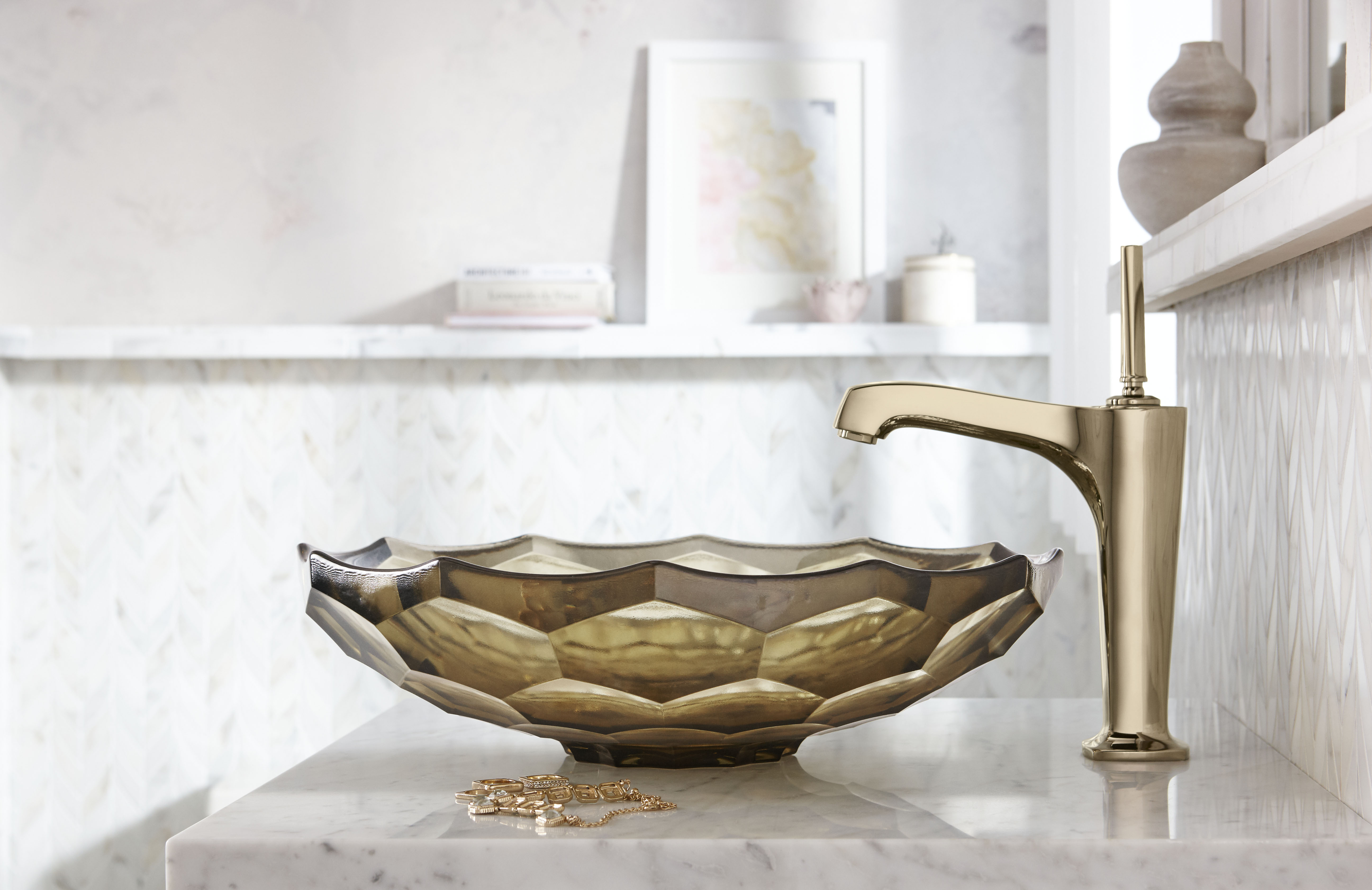 Margaux Faucet     Briolette Sink     The bright golden brown hues in this French Gold faucet and glass sink provide a nice visual contrast to this white space.