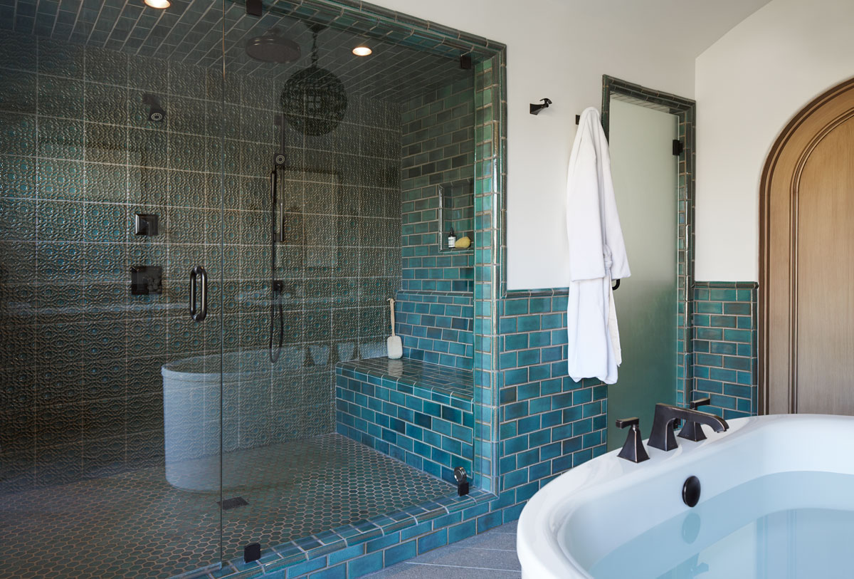 Sunstruck Freestanding Bath    Memoirs Bath Faucet    Traditional Rainhead    Memoirs Robehook    Memoirs Handshower    Rich blue-green tile gives the spacious master bath a watercolor, seaside appeal. The steam shower is a quiet dark space to be renewed with a soft mist.