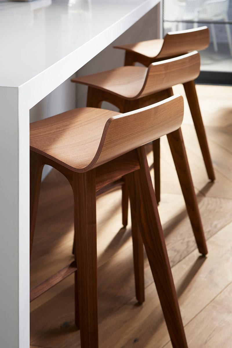 Silestone Iconic White Countertop      Contemporary bar stools play up the grainy sunburst textures of the wood floor, while creating an elegant contrast to the smooth, clean-lined countertops.