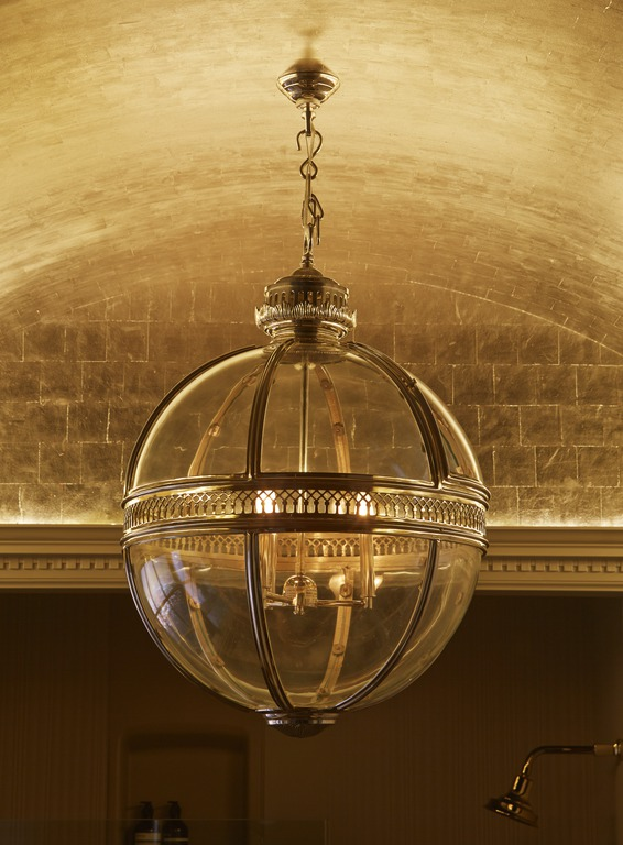 French Empire-style lighting casts a moody glow on textured gold leaf.