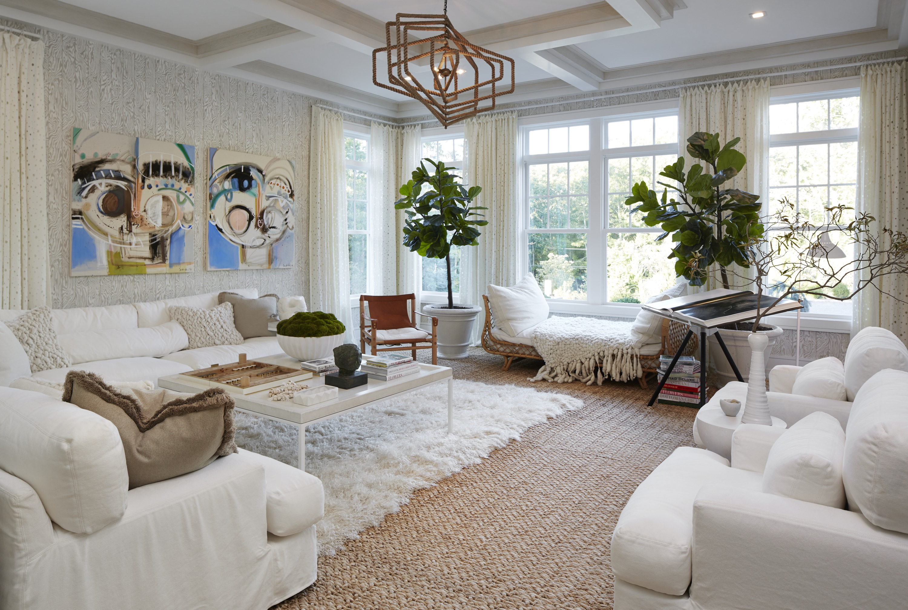 White overstuffed furniture, plush rugs and throws welcome guests into the home's first-floor living room with a casual crispness. Bold art pieces give the space a contemporary flair.