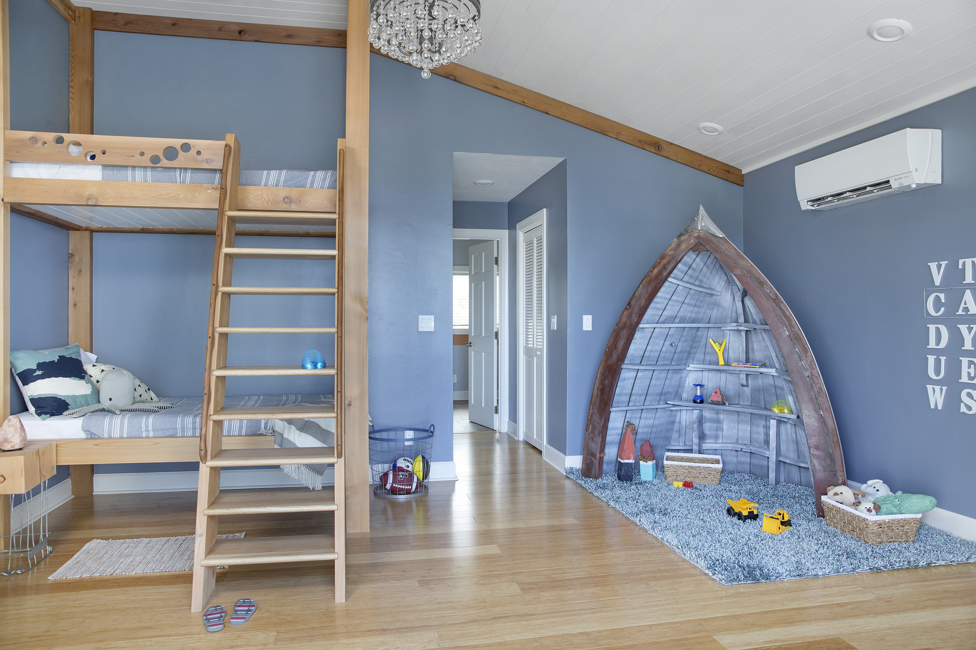A whimsical take on a nautical theme, this cheerful kids' room mixes ocean-blue walls with boat hull shelves and a ship-style V-groove ceiling.