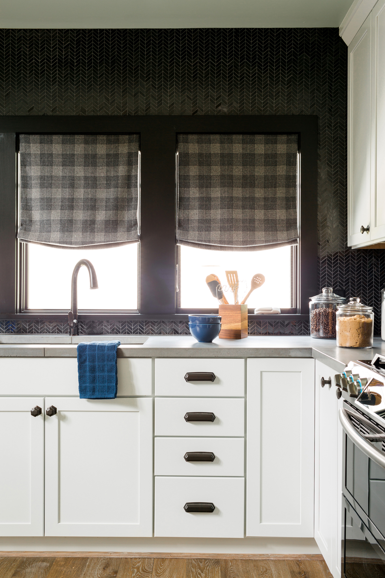Sensate® faucet   Prolific® kitchen sink     White lower cabinets have an expansive effect on the space, while a black chevron backsplash adds an element of luxury. An oil-rubbed bronze faucet blends seamlessly with the dark wall.