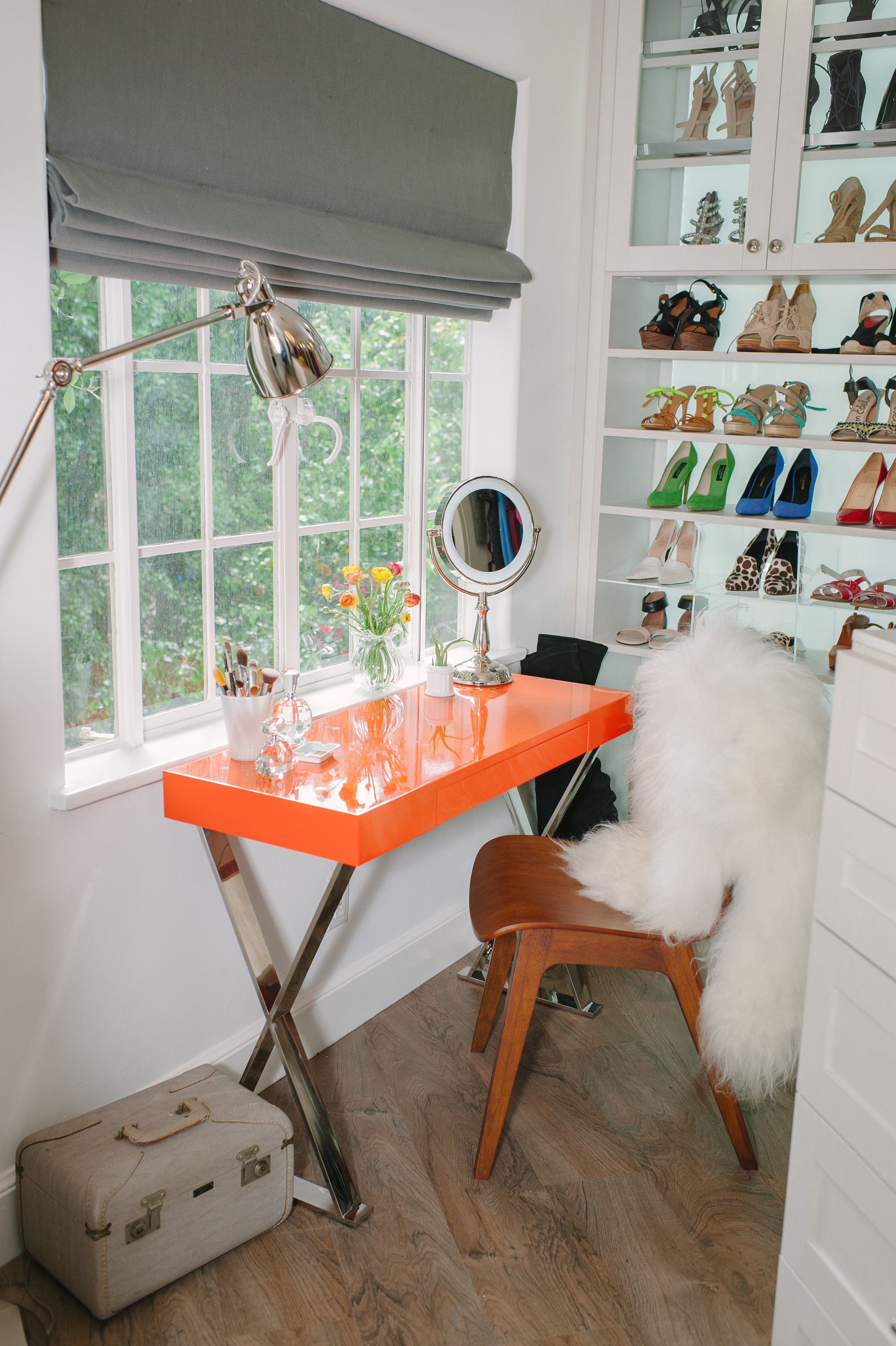 """Lewis placed a vanity near the window, so Thiessen can apply her makeup in natural light. She ordered the table from One King's Lane and had it lacquered in the same signature shade as the Hermes boxes in Thiessen's closet. """"Tiffani was drawn to that color, it was absolutely fashion-inspired,"""" says Lewis."""