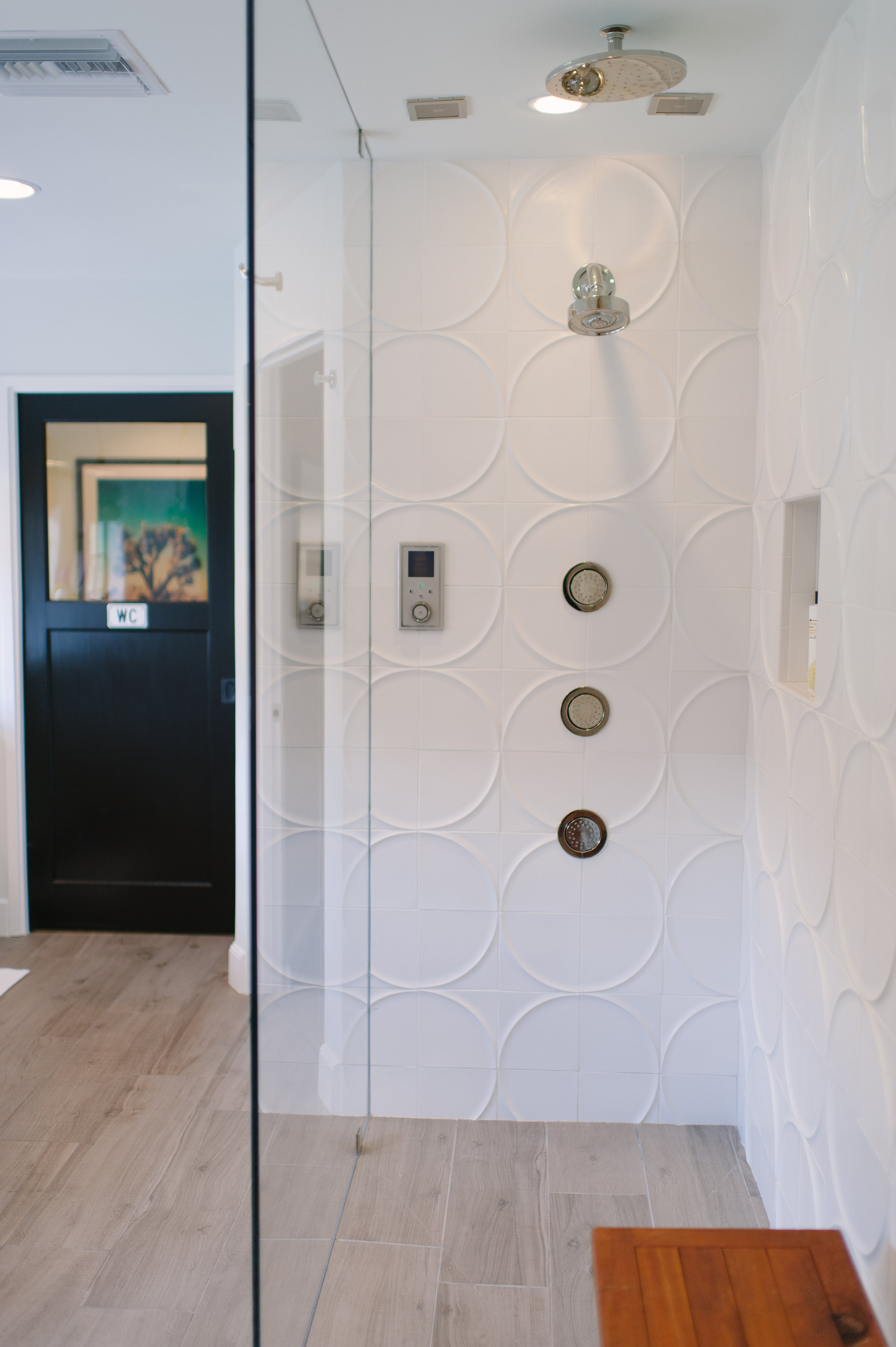 WaterTile Bodysprays   Round rainhead   Purist showerhead   Ann Sacks wall tile    The shower is simple yet luxurious, with graphic circle wall tile, two showerheads, and a trio of bodysprays.