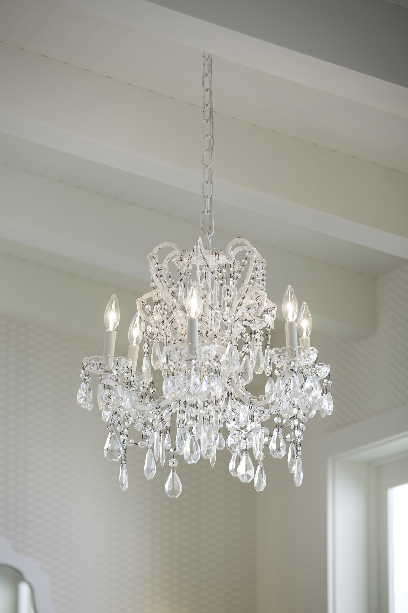 An ornate light fixture adds a surprising yet beautiful contrast to a subtly patterned wallpaper.