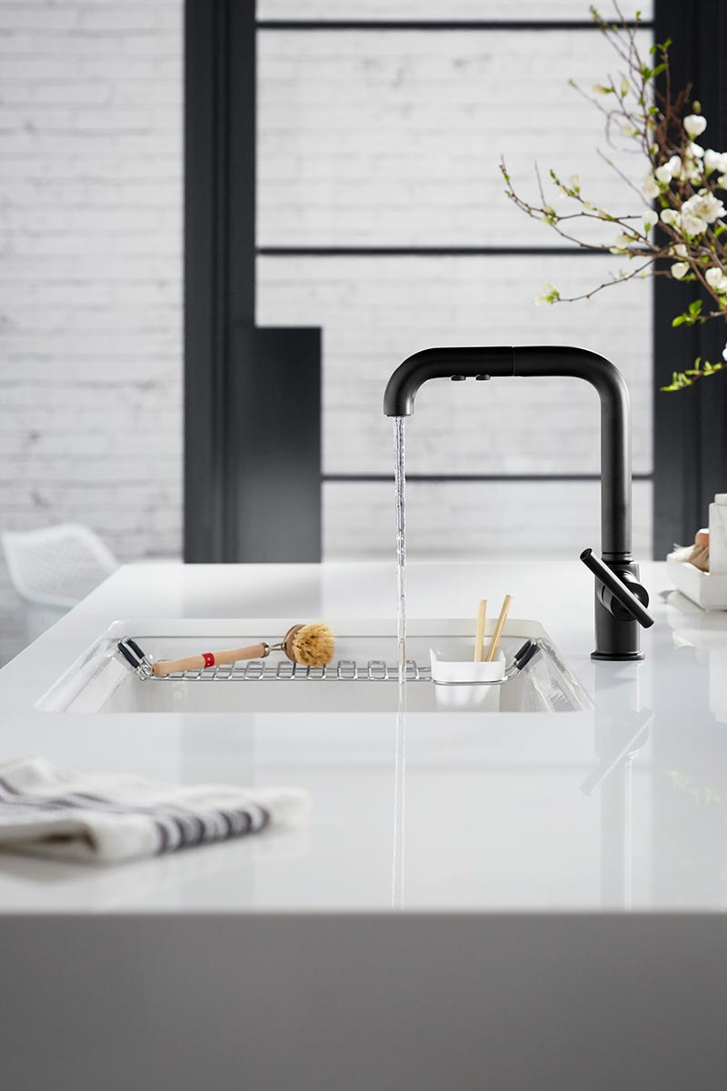 Purist Faucet     Riverby Sink     Silestone Iconic White Countertop      An under-mount sink blends right into the countertop, while the faucet's sleek style harmonizes with the black trim in the background.