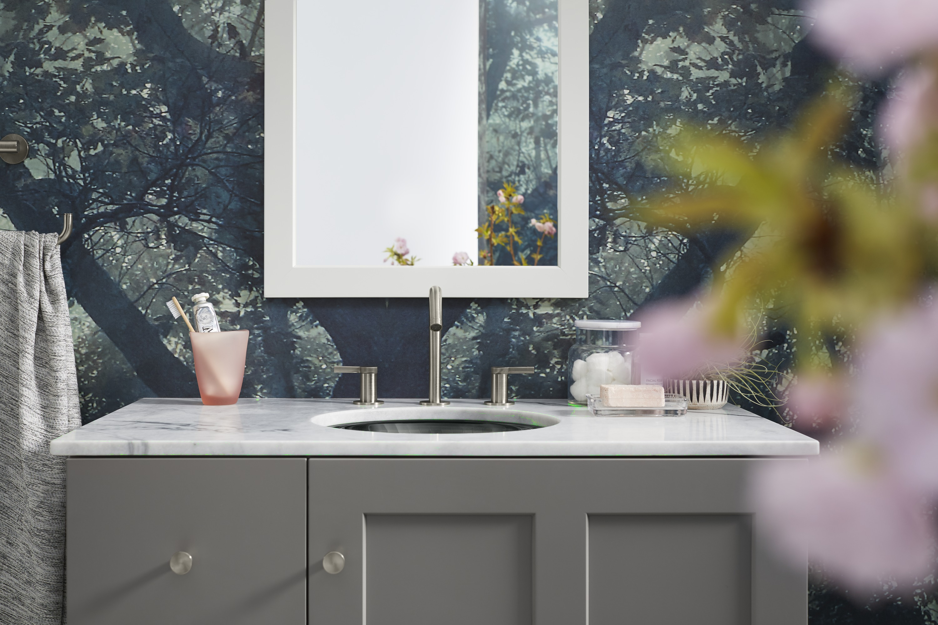 Purist® cabinet knob     Poplin® mirror     Stillness® faucet     A light gray vanity and white mirror add brightness to a small space.