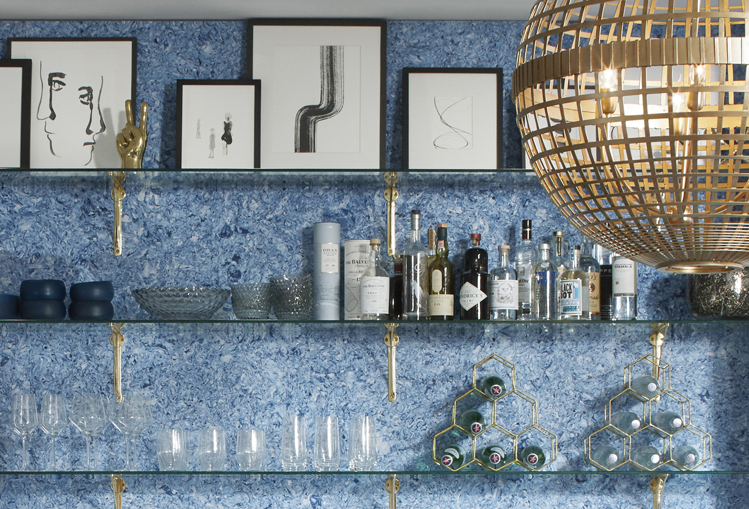 Using the bright blue wall material she designed, Kerrie Kelly created a vibrant backdrop for open shelving with a curated collection of glass and artwork.