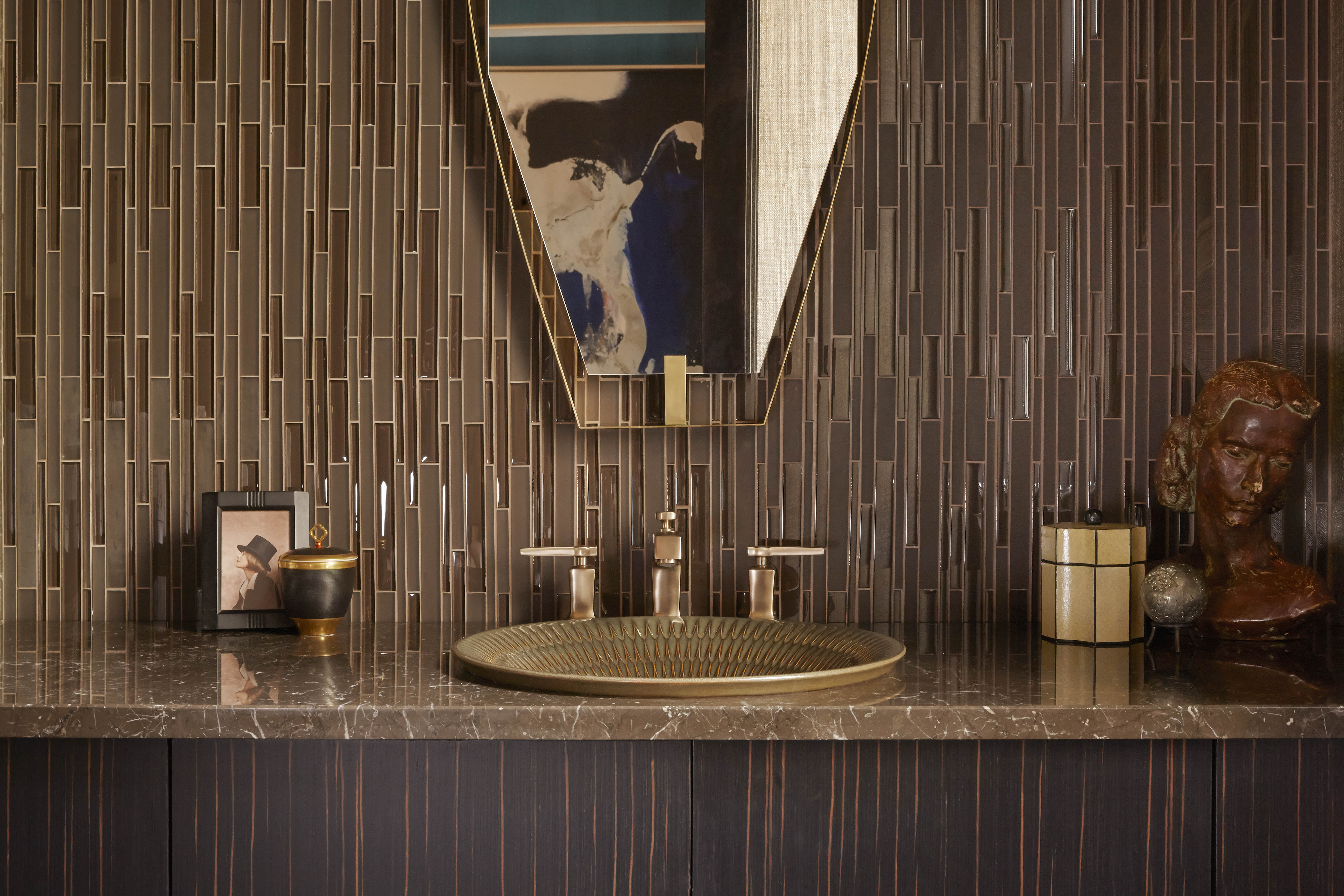 Derring™ sink     Margaux® faucet     Brown and bronze finishes throughout the space have a warm, natural feel.