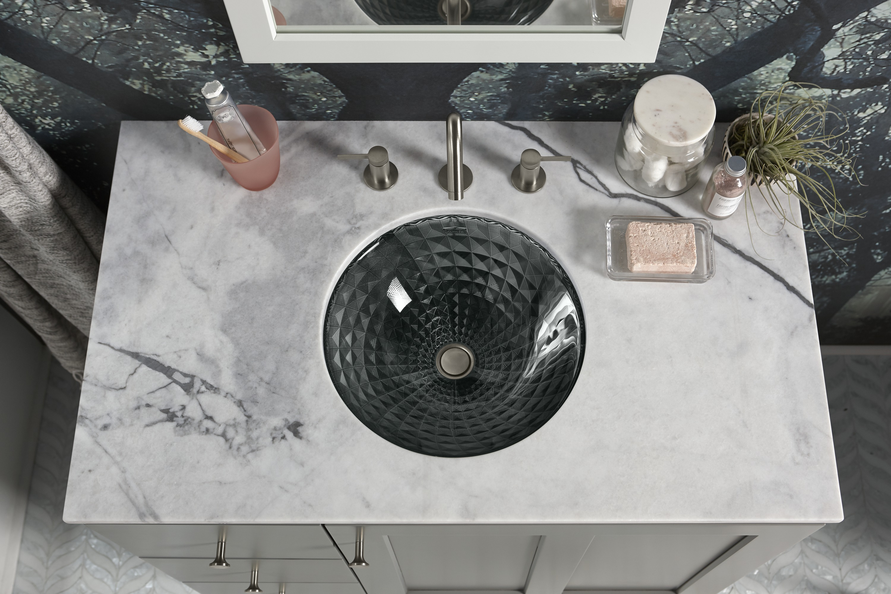Stillness® faucet     Kallos® sink     A faceted glass sink reflects the room's moody depth.