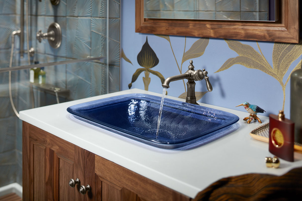 Inia Sink    Artifacts Faucet    Damask Vanity    Solid/Expressions Vanity Top    A dark sapphire-colored sink draws out the deep hues in the bathroom's botanical wallcovering and complement the plum walls.