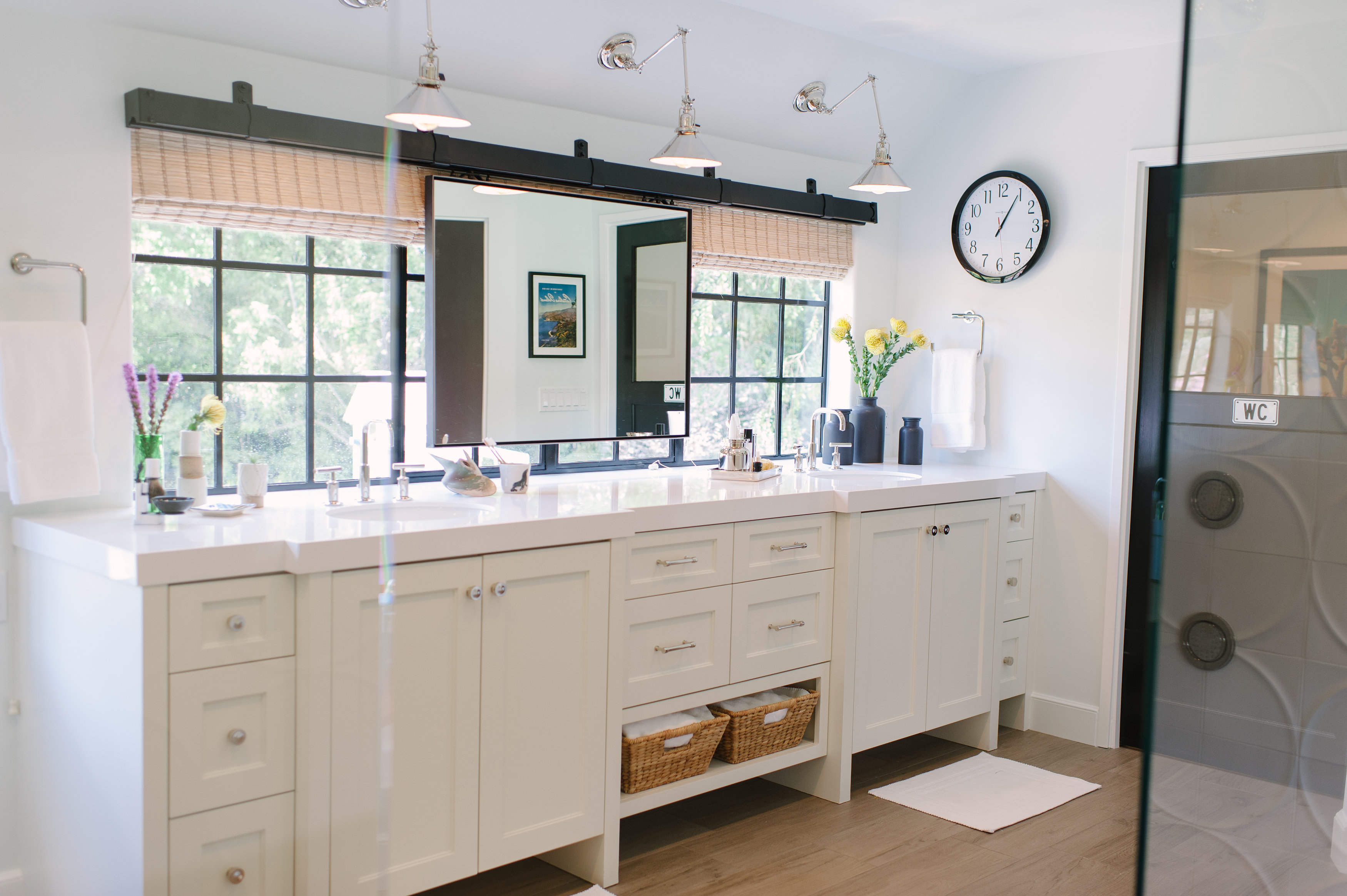 Purist faucets    To bring more light into the master bathroom, Lewis added a nine-foot window. The mirror slides back and forth on a barn-door track, so the couple can share it.