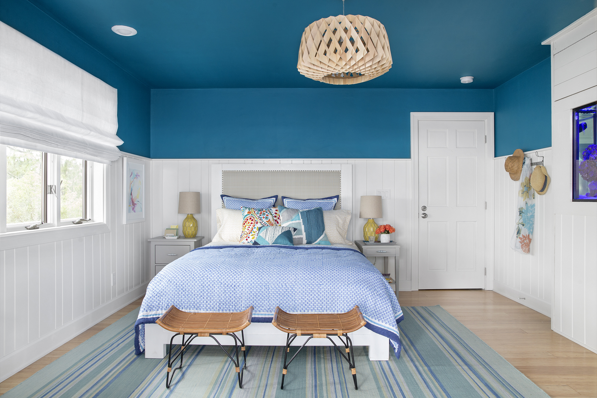 Azure paint, white beadboard paneling and taupe accents give the guest bedroom a crisp, beachy freshness, while modern rattan-style stools offer guests extra convenience.