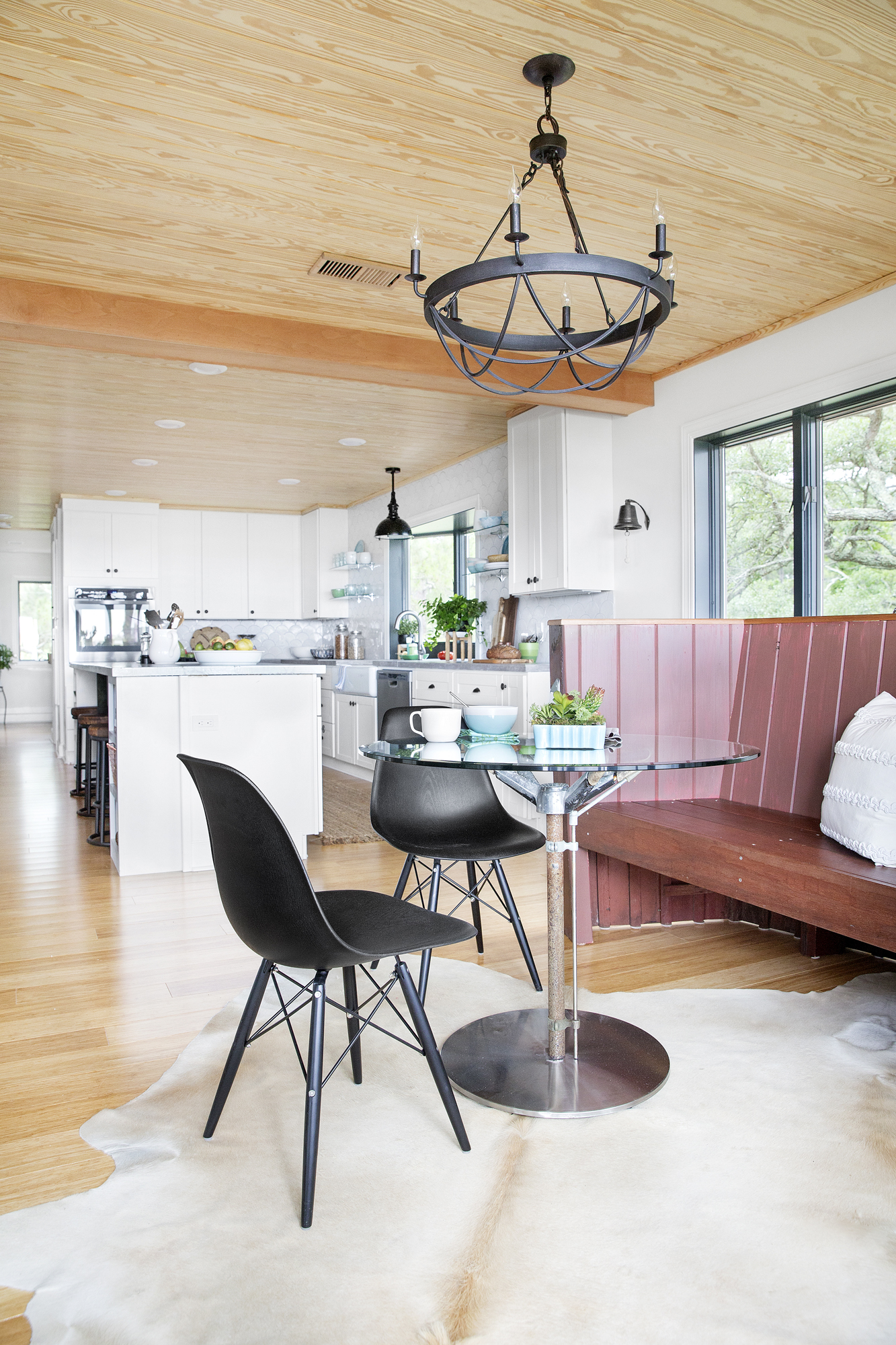 Open to the kitchen and living areas, the breakfast nook pairs the hull of a restored 19th-century mahogany boat with modern details like Eames-style dining chairs.