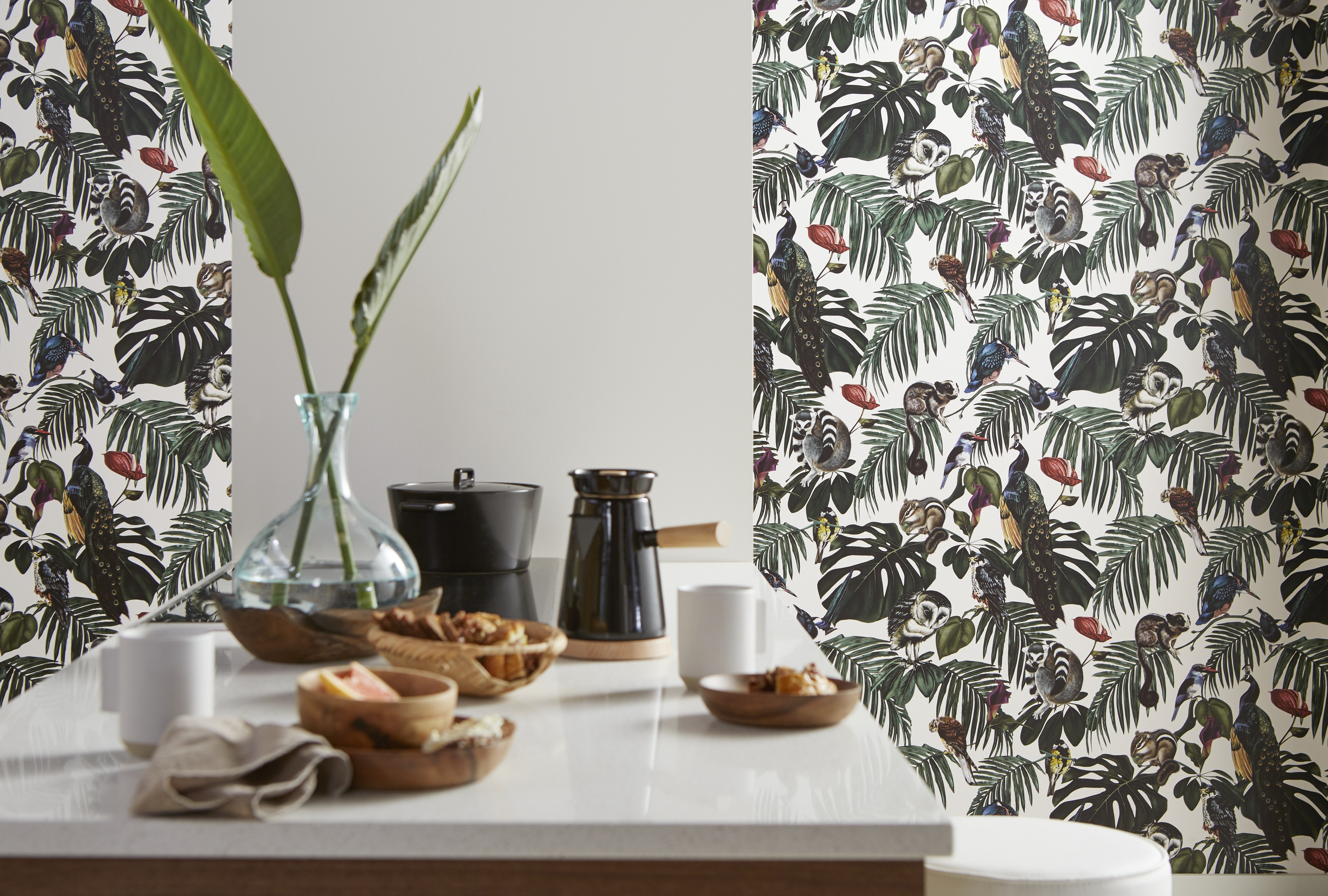 Paired with a solid-color countertop and wall, playful flora and fauna wallpaper creates a feeling of adventure without feeling overwhelming.