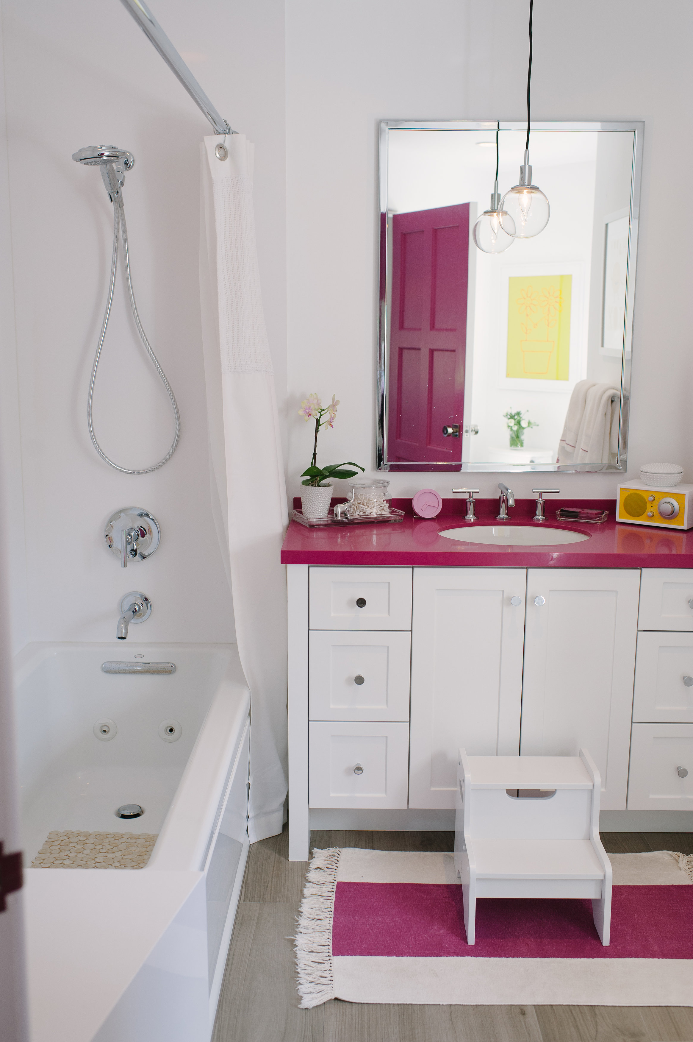 """Purist faucet   Verticyl sink   Flipside handshower   Archer bath    Designer Kim Lewis brought the magenta color into Harper's bathroom in a big way. """"I let the rest of the space breathe with white tile,"""" she says."""
